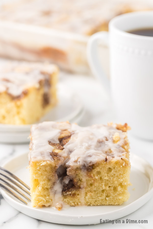 A piece of the cinnamon roll cake on a white plate with a fork next to it with a cup of coffee.
