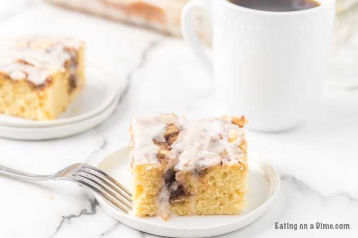 A piece of the cinnamon roll cake on a white plate with a fork with another piece on a plate in the back ground.