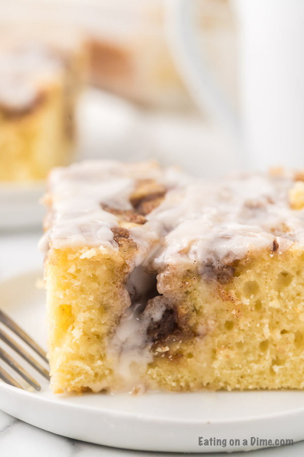 A close up of the cinnamon roll cake on a white plate