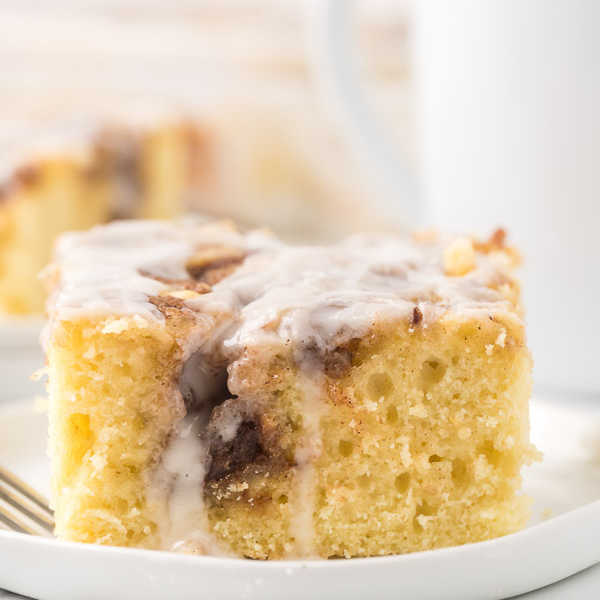 A close up of the cinnamon roll cake on a white plate with a cup of coffee behind it.