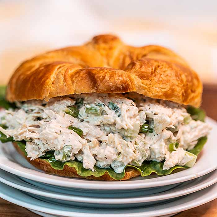 Close up image of chicken salad on croissant on a white plate.