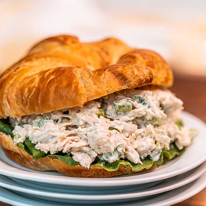 Close up image of chicken salad on a croissant on a plate.