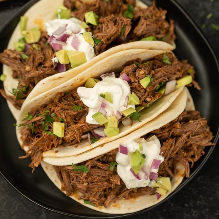 mexican shredded beef tacos on plate