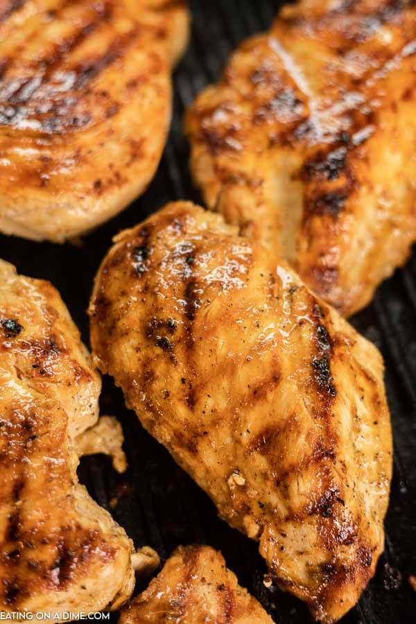 4 chicken breasts on a grill.