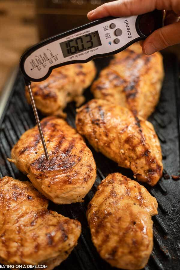 Chicken breasts on a grill with a meat thermometer entered into one chicken breasts with a reading of 160.3 degrees F.