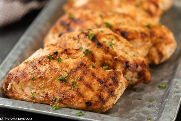 Close up of grilled chicken breasts on a silver platter topped with fresh parsley.