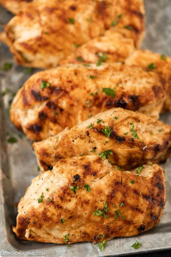 Grilled chicken breasts on a silver platter.