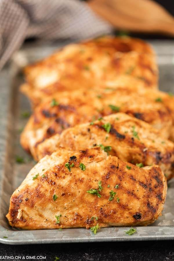 5 grilled chicken breasts on a silver platter topped with fresh chopped parsley.