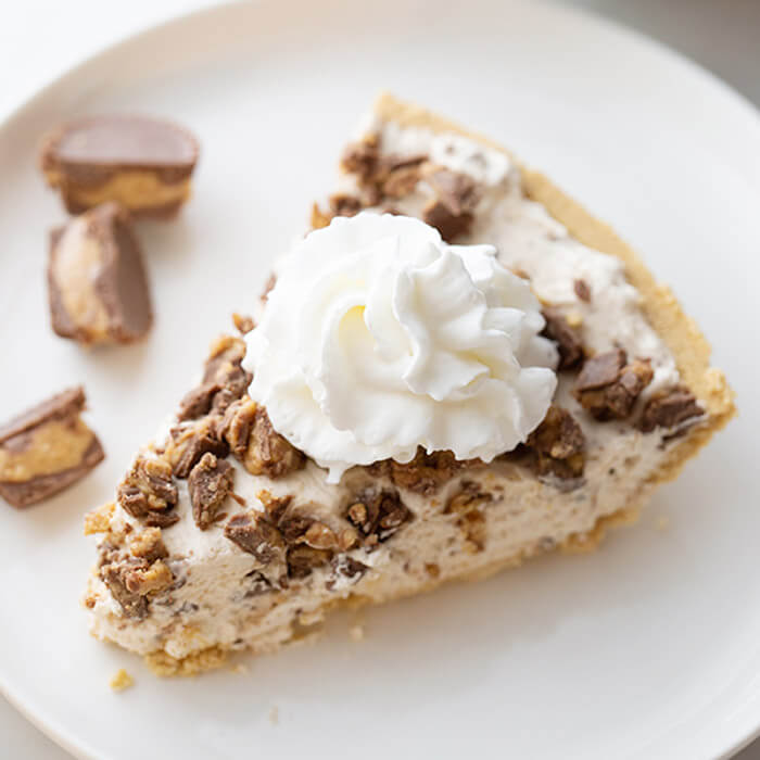 Close up image of Reese's Cup peanut butter pie on a plate. With Reese's Cups on the side.
