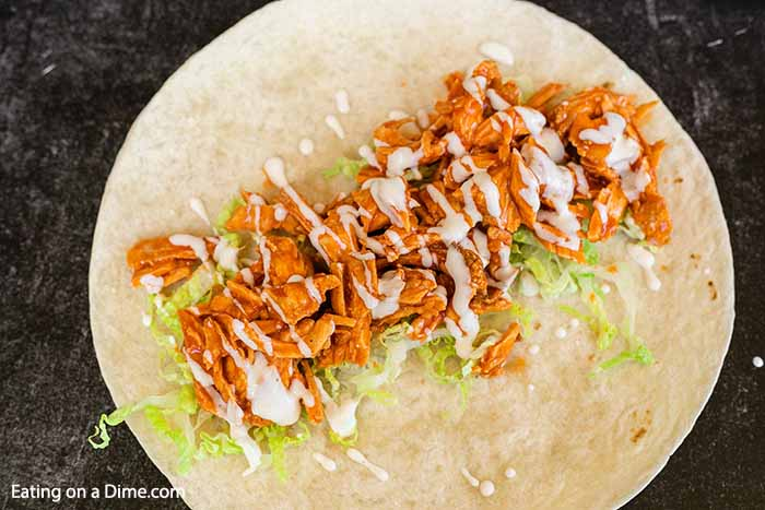 Make this delicious Buffalo chicken wrap recipe in just 5 minutes! Lots of buffalo flavor and ranch make buffalo chicken wraps recipes spicy and delicious. Try buffalo chicken wraps healthy and easy. Top with shredded lettuce and enjoy! #eatingonadime #buffalochickenwraprecipe