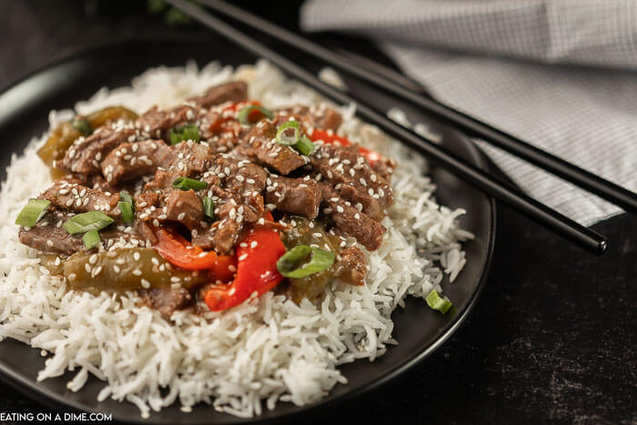 A plate of this pepper steak over rice on a black plate with chop sticks next to the plate.