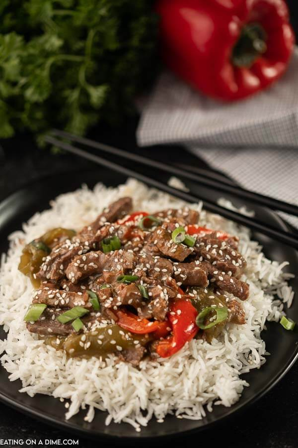 A black plate topped with rice and this crock pot pepper steak with peppers on top of the rice.