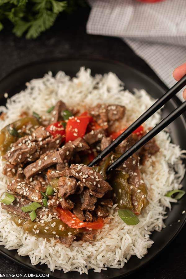 A plate filled with rice and then this crock pot pepper steak on top with chop sticks picking up some of the pepper steak.