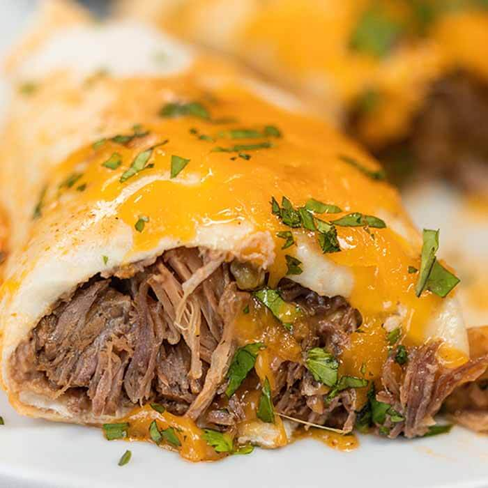 Crock pot smothered burritos will be a family favorite. Tender beef smothered with cheese and more make this green chili recipe so flavorful. The crockpot makes it simple and easy. This crock pot Mexican recipe for smothered burritos has the best green sauce. #eatingonadime #crockpotsmotheredburritos #slowcooker