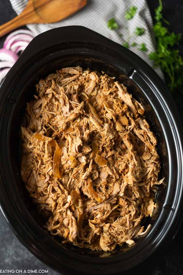Overview of the shredded pulled pork in a crock pot with red onions and parsley in the back ground