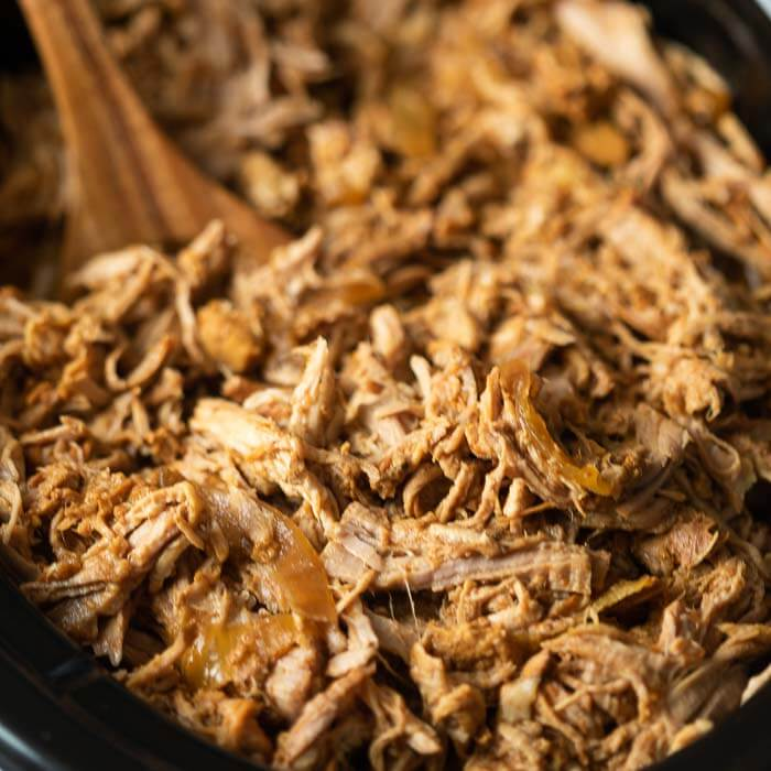 Shredded BBQ pulled pork and onions in a black crock pot