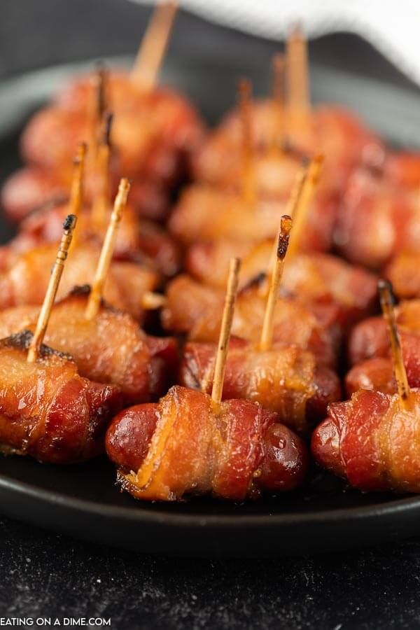 Close up image of Bacon wrapped lil smokies with toothpicks in them.