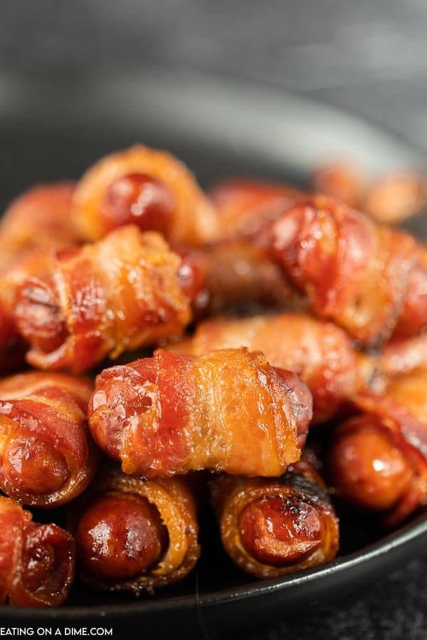 Close up image of bacon wrapped lil smokies on a black plate.
