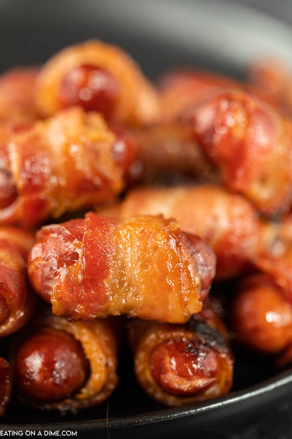 close up image of bacon wrapped lil smokies on a black platter.