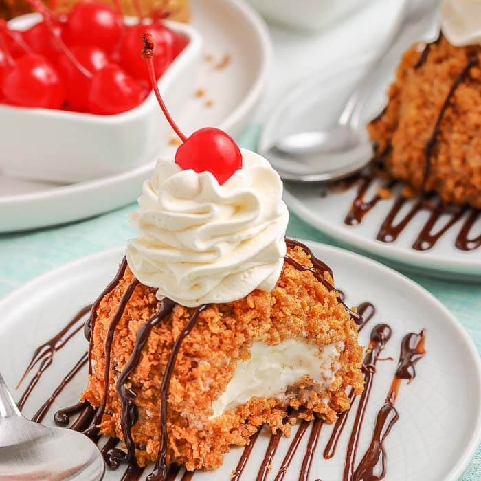 Fried Ice Cream on a white plate topped with whipped cream and a cherry with more cherries behind it