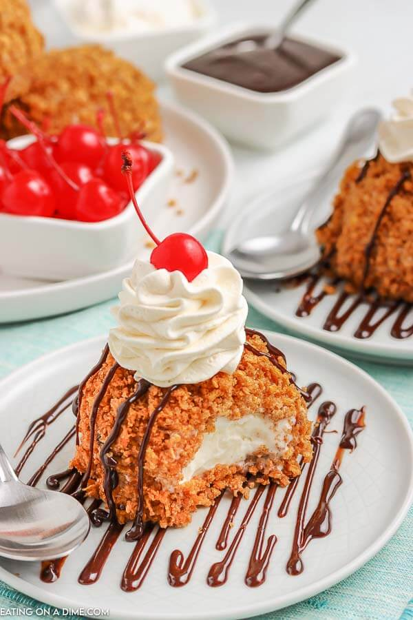 Fried Ice Cream on a white plate topped with whipped cream and a cherry.