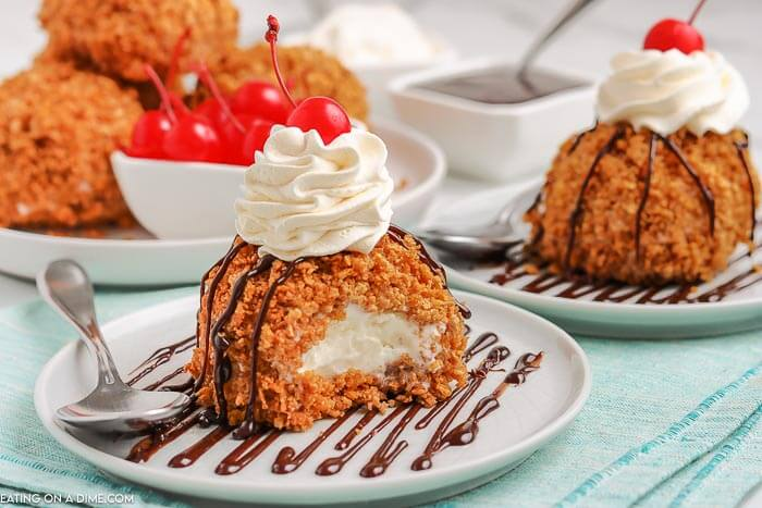 Fried Ice Cream on a white plate topped with whipped cream and a cherry. There is 1 bite taken out of the ice cream and there is another fried ice cream on a plate behind it as well.