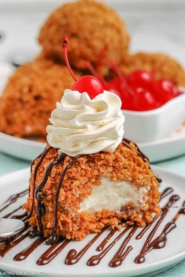 Fried Ice Cream on a white plate topped with whipped cream and a cherry. There is 1 bite taken out of the ice cream