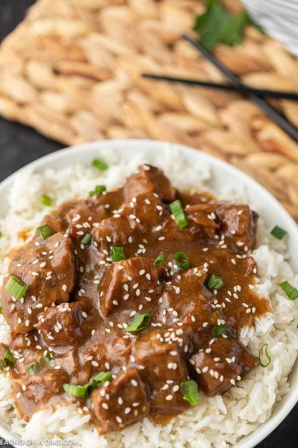 Instant Pot Teriyaki Beef over rice topped with green onions and sesame seeds with chop sticks in the back ground