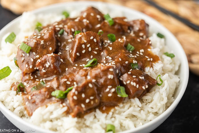 A white bowl full of rice topped with teriyaki beef topped with green onions