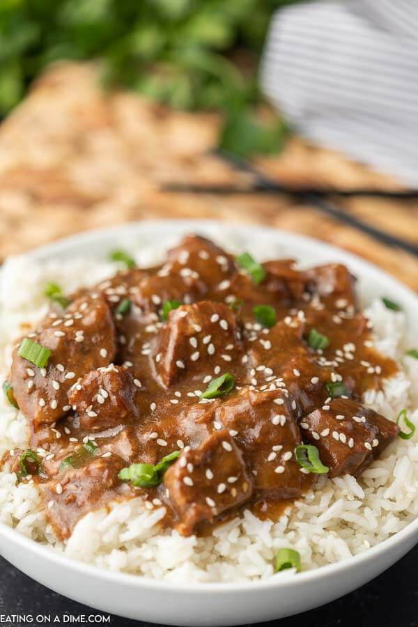 Teriyaki Beef over rice with chop sticks in the back ground