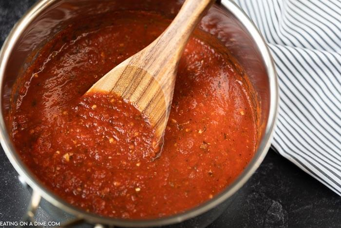 a sauce pan of marinara sauce with a spoon in it and a striped towel next to it