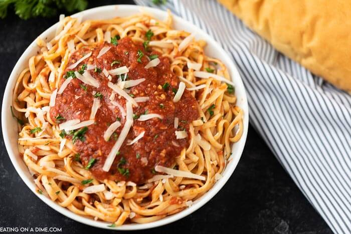 A bowl of pasta topped with marinara sauce and parmesan cheese with french bread next to it