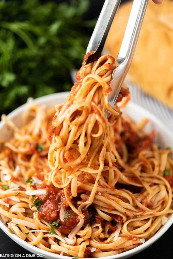 Tongs serving pasta covered in marinara sauce
