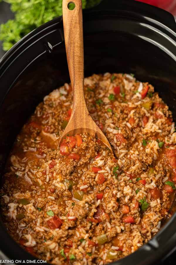 Close up image of stuffed pepper soup in a crock pot with a brown spoon.