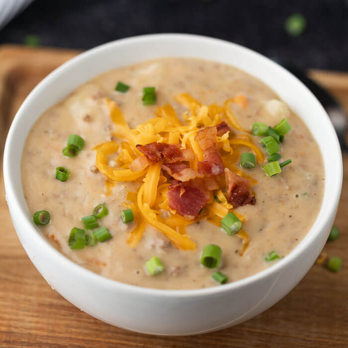bowl of cheeseburger soup topped with bacon, green onion and shredded cheese