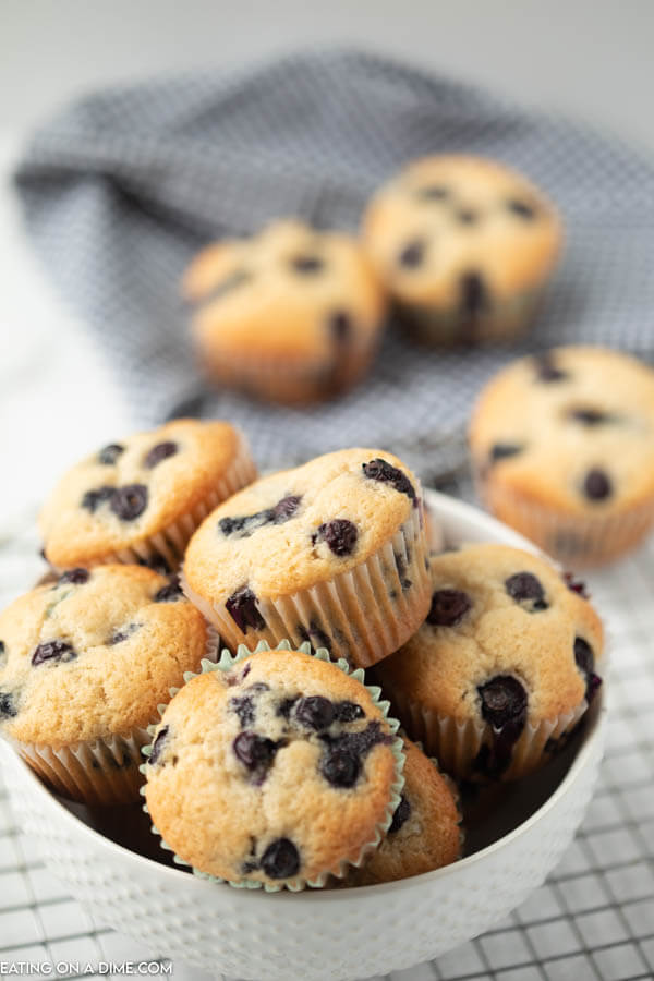 Blueberry Muffins in a white bowl with more muffins behind it on a cooling rack.