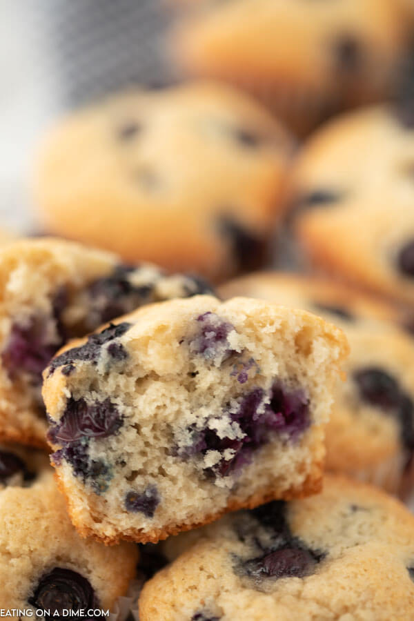 Blueberry muffins stacked on top of each other with the top one cut in half.