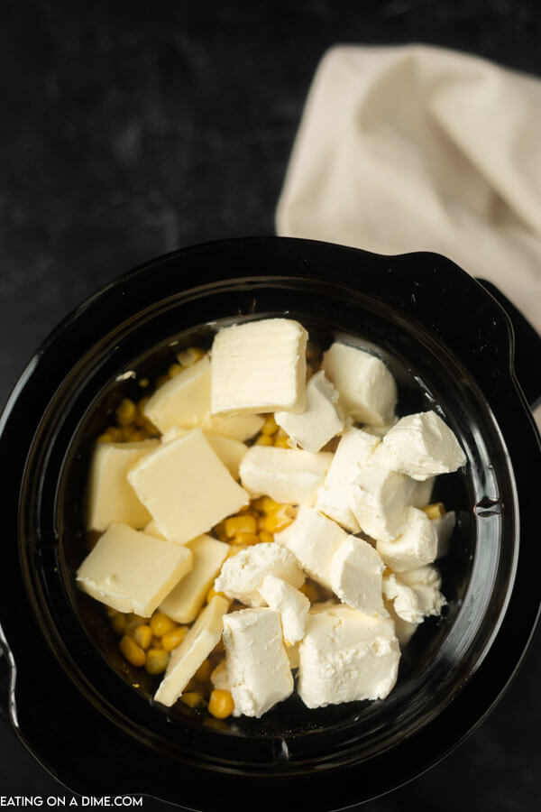 corn, butter and cream cheese in crockpot ready to be cooked