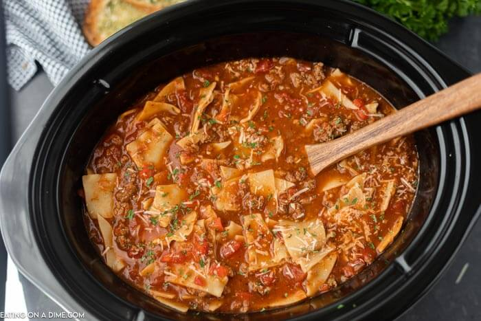 a crock pot full of this lasagna soup with a wooden spoon in it