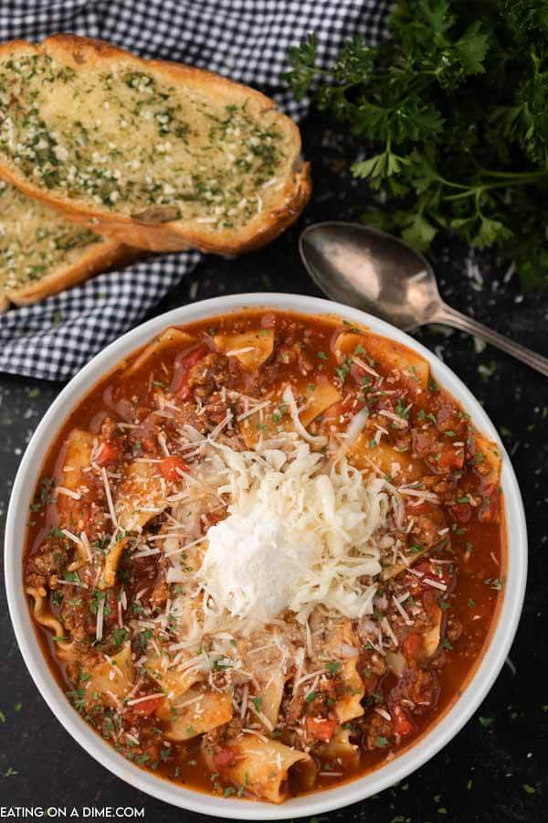 A bowl of the lasagna soup topped with ricotta cheese and parmesan cheese.