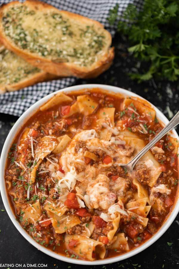 A bowl of lasagna soup with a spoon in it scooping a bite out of the soup!