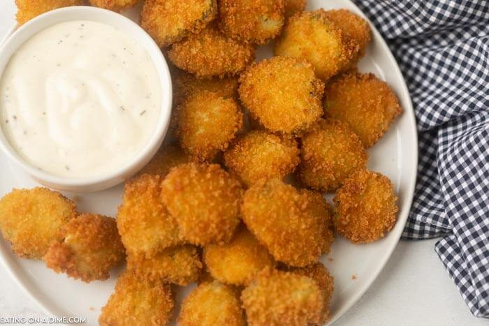 fried pickles on a plate with ranch dipping sauce