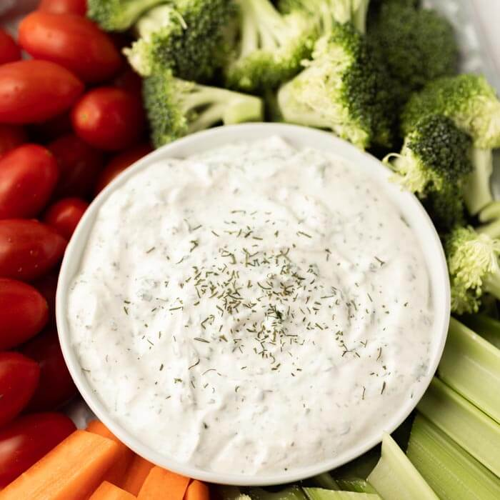 ranch dip in a bowl with vegetables around it