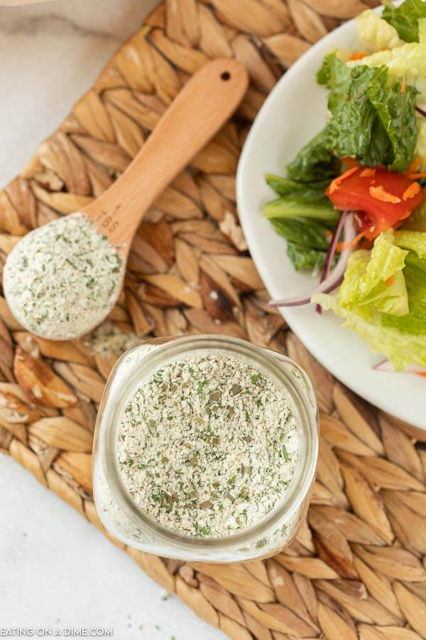 A jar of the ranch seasoning mix nex to a salad with a tablespoon of the mix next to it as well.