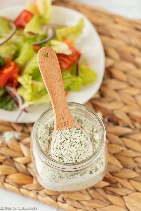 A tablespoon in a jar of the ranch seasoning mix scooping out some of the mix with a salad in the back ground.