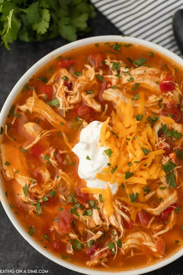 Close up image of a bowl of chicken fajita soup with sour cream on top.