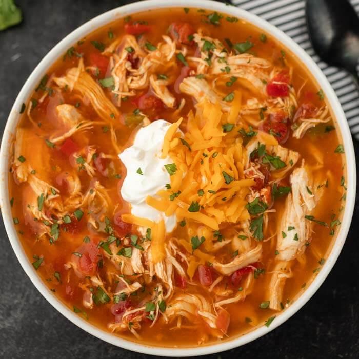 Close up bowl of chicken fajita soup in a white bowl.