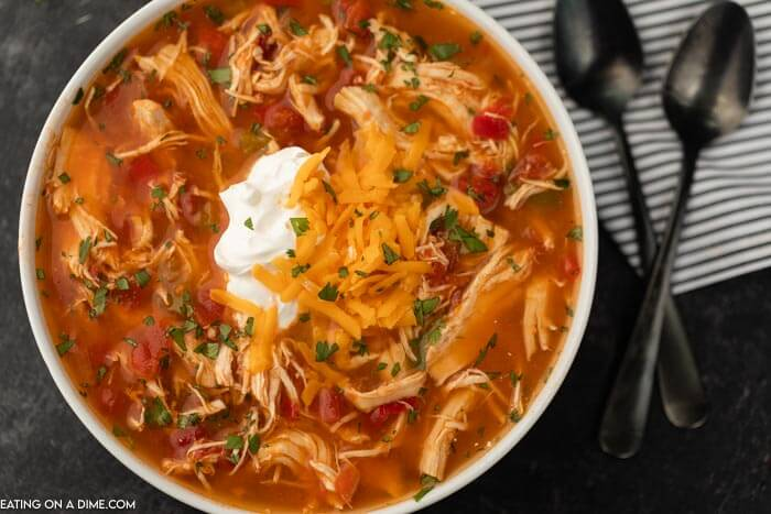 Close up image of a bowl chicken fajita soup in a white bowl with two black spoons.