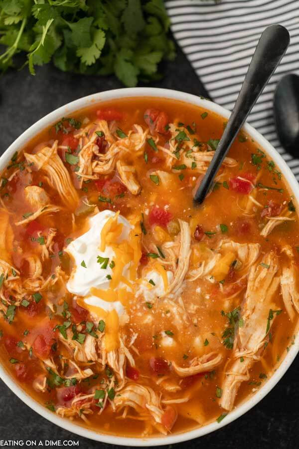 Close up image a bowl of chicken fajita soup in a white bowl with black spoon in it.
