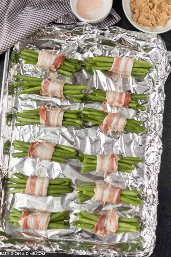 green bean bundles on baking sheet ready to go in the oven
